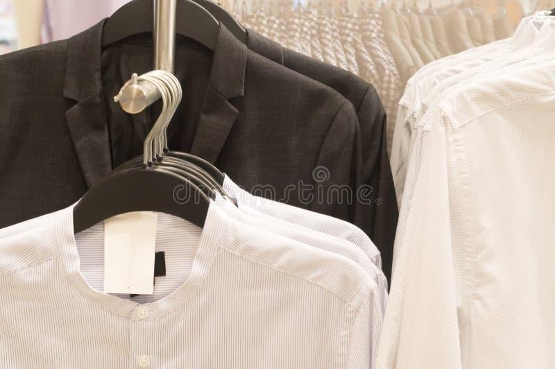 Ternos pretos e camisas brancas que articulam-se em ganchos imagens de stock