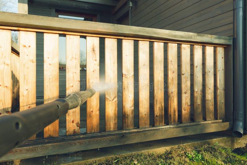 Terraço de limpeza com uma arruela do poder - líquido de limpeza do homem da pressão de ponto alto em trilhos de madeira do terra imagens de stock