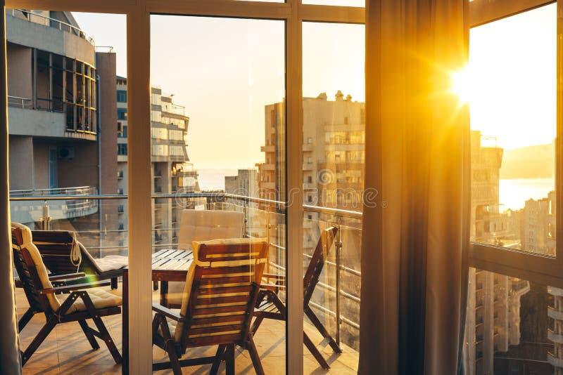 Terraço do verão com mobília do jardim no fundo da cidade e do por do sol verão Concep da recreação do recurso de Luxuary Apatram foto de stock