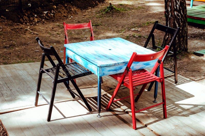 Terraço exterior do verão do restaurante - café do vintage com a tabela azul velha com as cadeiras pretas e vermelhas foto de stock royalty free