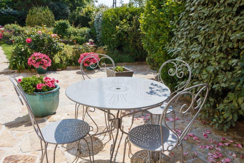 Terraço florescido com mobília do jardim fotos de stock royalty free