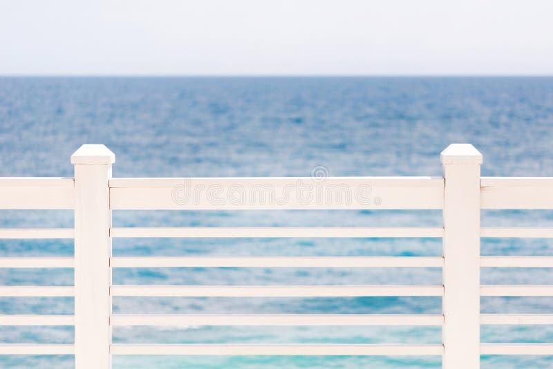 Terraço ou balcão com a cerca branca de madeira, o mar ou o oceano e céu claro, fundo do seascape Copyspace foto de stock royalty free