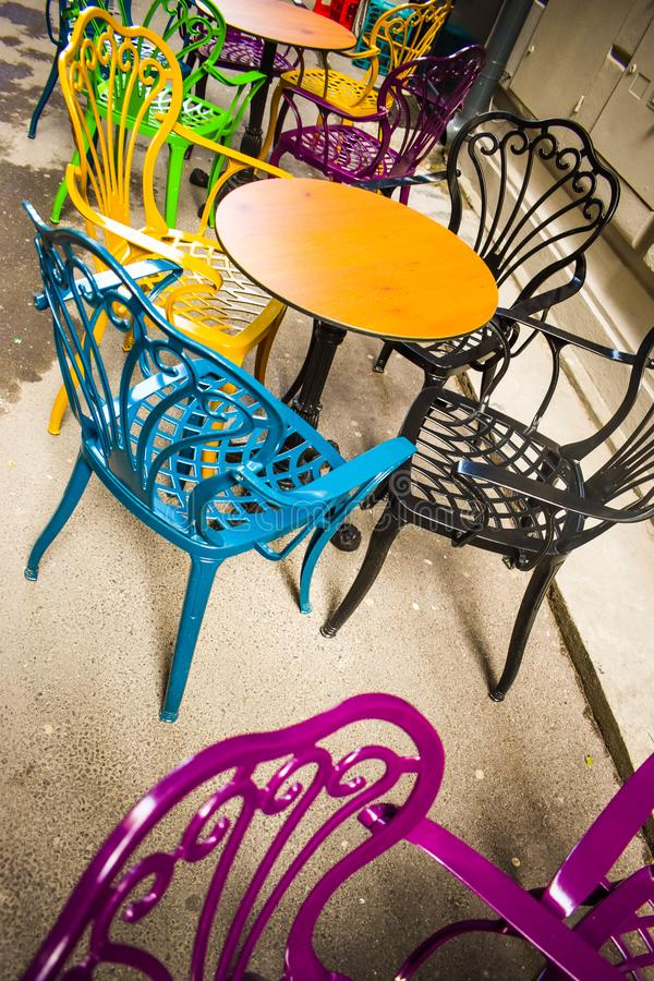 Terraço vazio do vintage na baixa histórica com as cadeiras multi-coloridas no passeio do pavimento Cadeiras coloridas em retro fotos de stock