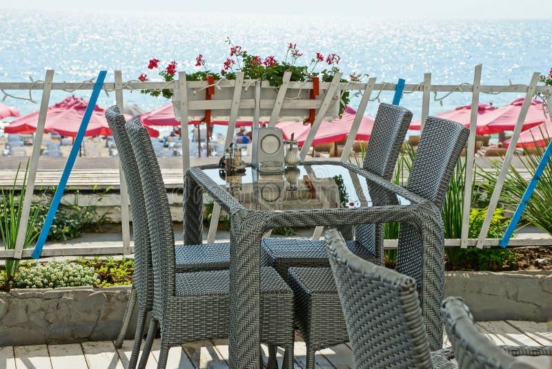 Terraços de um restaurante do verão com cadeiras cinzentas e de uma tabela de vidro pela cerca contra o mar fotografia de stock