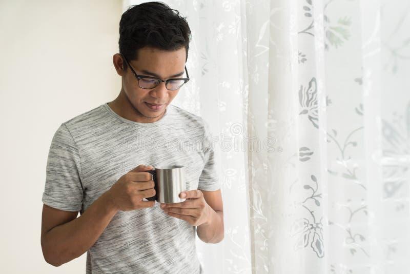 Terra arrendada adolescente asiática uma caneca com as bebidas quentes na manhã imagens de stock