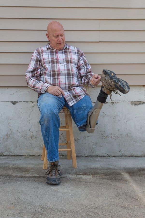 A terra arrendada assentada do homem do amputado girou o pé protético acima pelo laço da sapata imagens de stock royalty free