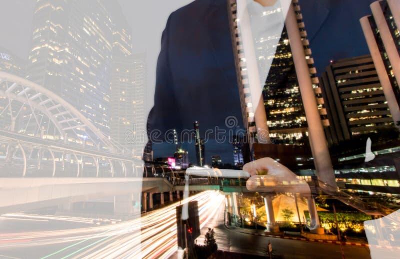 Terra arrendada da mão do homem de negócios da exposição dobro e telefone esperto do tela táctil com fundo moderno da cidade Móbi fotografia de stock royalty free