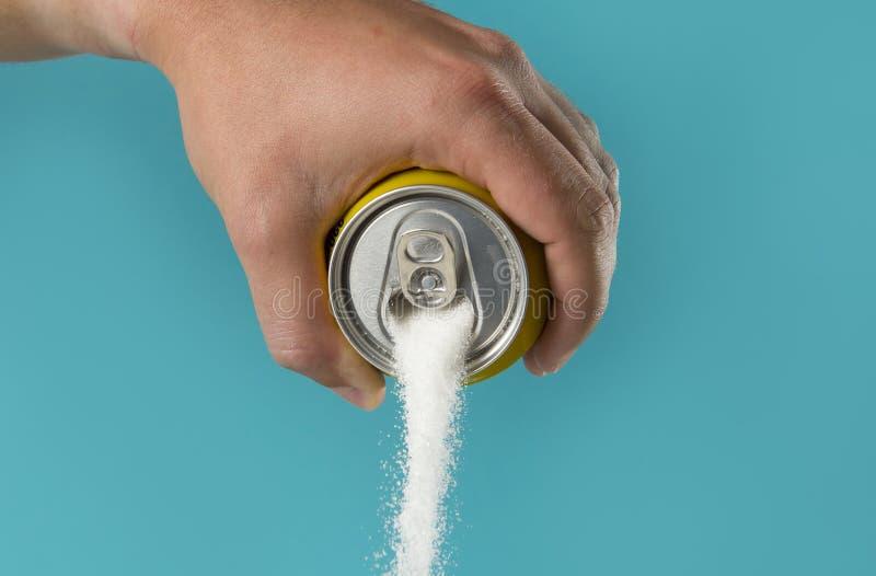 A terra arrendada da mão do homem refresca a bebida pode córrego de derramamento do açúcar no doce e de conteúdo em calorias de b foto de stock
