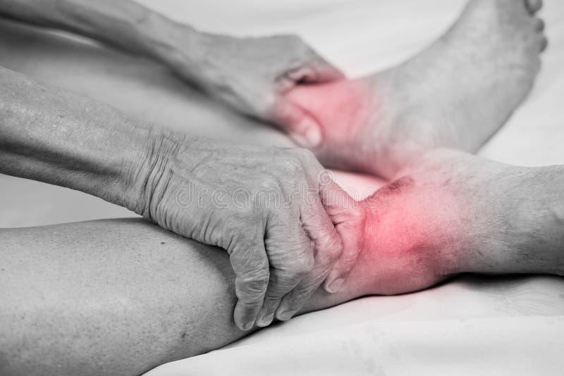 Terra arrendada da mão do homem superior ele pé e tornozelo saudáveis da massagem em p imagem de stock royalty free