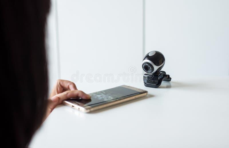 A terra arrendada da mão e o móbil da imprensa conectam a câmara de segurança, CCTV do relógio do telefone imagens de stock