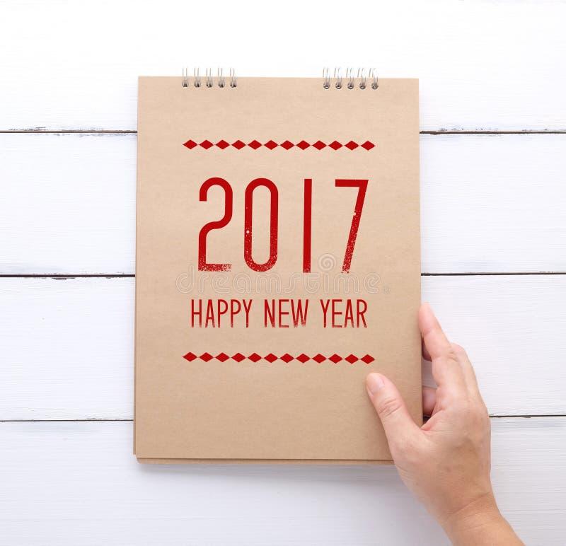 A terra arrendada da mão recicla o caderno de papel com ano novo feliz 2017 sobre foto de stock royalty free