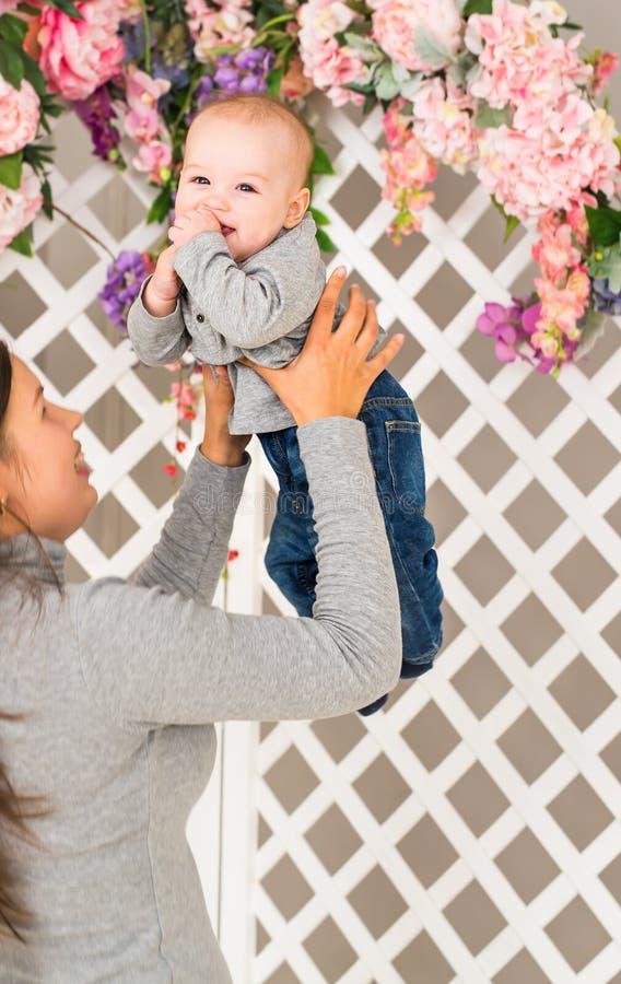 Terra arrendada da matriz sua criança Mamã que joga com criança de riso Família em casa fotos de stock