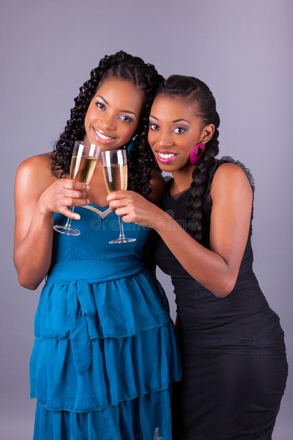 A terra arrendada da mulher africana bonita nova um o vidro do champanhe imagem de stock