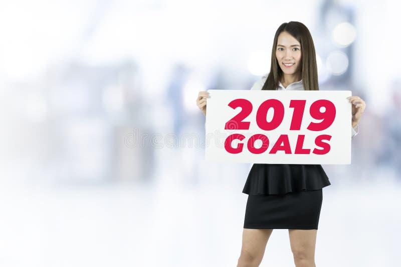 A terra arrendada da mulher de negócios afixa 2019 objetivos assina imagens de stock royalty free