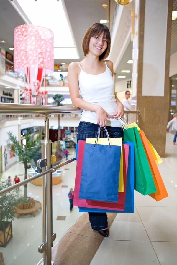 Terra arrendada da mulher nova em sacos multi-coloured das mãos fotos de stock