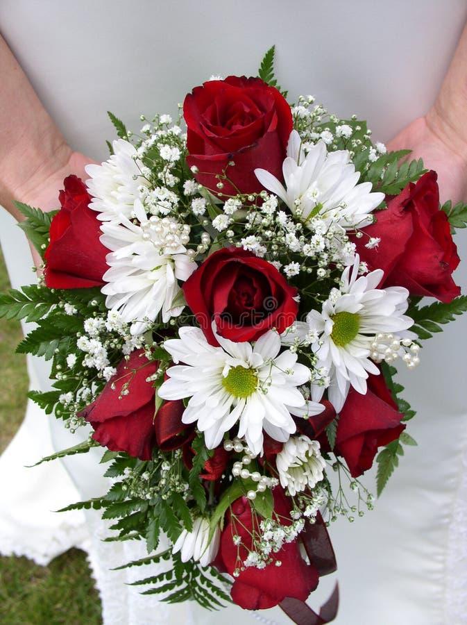 Terra arrendada da noiva seu ramalhete do casamento de encontro a seu vestido foto de stock royalty free