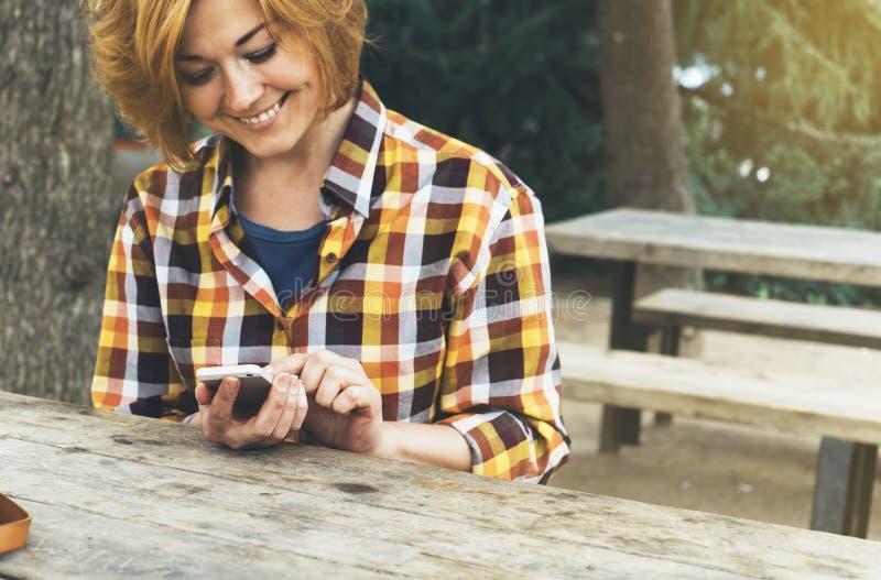 Terra arrendada da pessoa do moderno nas mãos telefone esperto móvel digital, leitura do sorriso da moça no dispositivo na paisag foto de stock royalty free