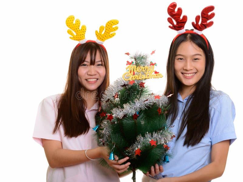 Terra arrendada de sorriso Cristo alegre de dois adolescentes asiáticos felizes novos foto de stock