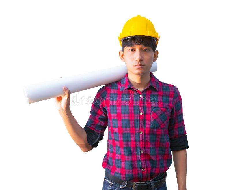 A terra arrendada do coordenador rolou a construção dos modelos no ombro e veste o plástico amarelo do capacete de segurança no f fotografia de stock