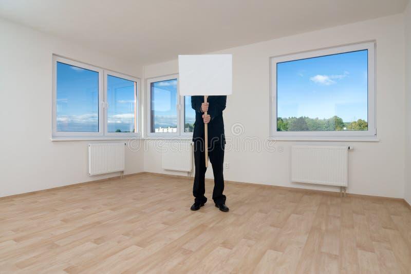 A terra arrendada do homem assina dentro o quarto vazio imagem de stock