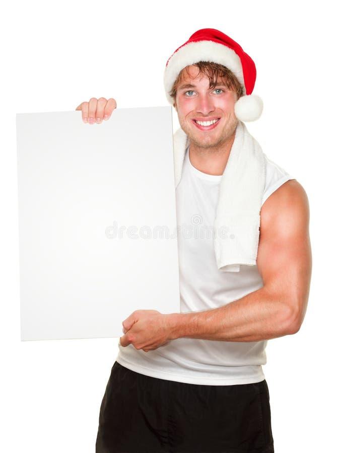 A terra arrendada do homem da aptidão assina dentro o chapéu de Santa do Natal imagens de stock