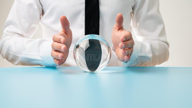 A terra arrendada do homem de negócios protetora cede uma bola de cristal foto de stock