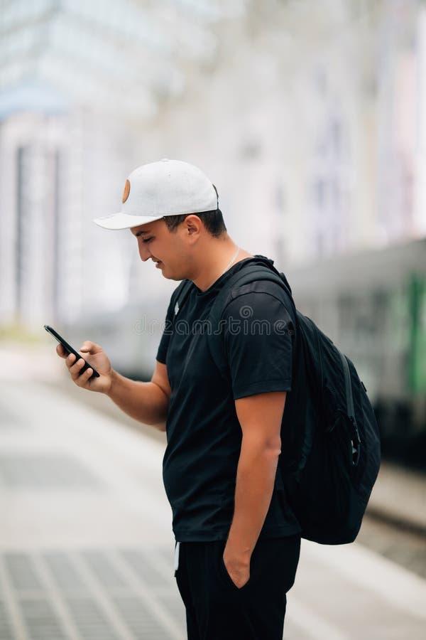 Terra arrendada do homem novo usando o telefone com posição da trouxa na plataforma no estação de caminhos de ferro Conceito do c imagem de stock royalty free