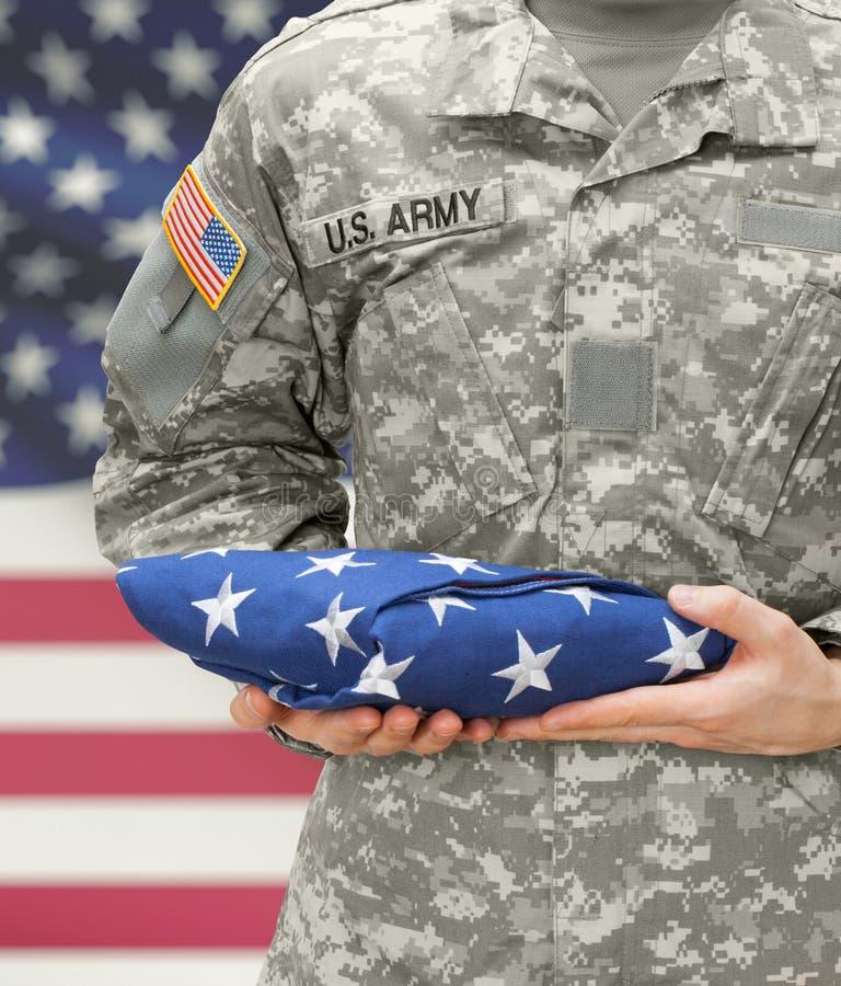 A terra arrendada do soldado do exército dos EUA dobrou a bandeira dos EUA antes de sua caixa imagem de stock
