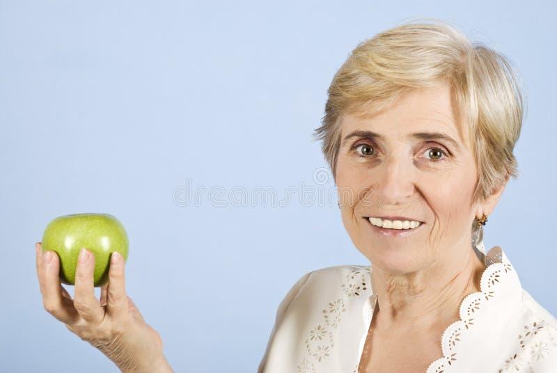 Terra arrendada e maçã sênior da mulher foto de stock