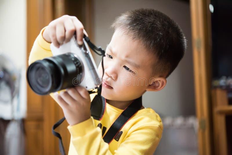 A terra arrendada e o tiro bonitos novos do menino uma foto pela câmera branca imagem de stock