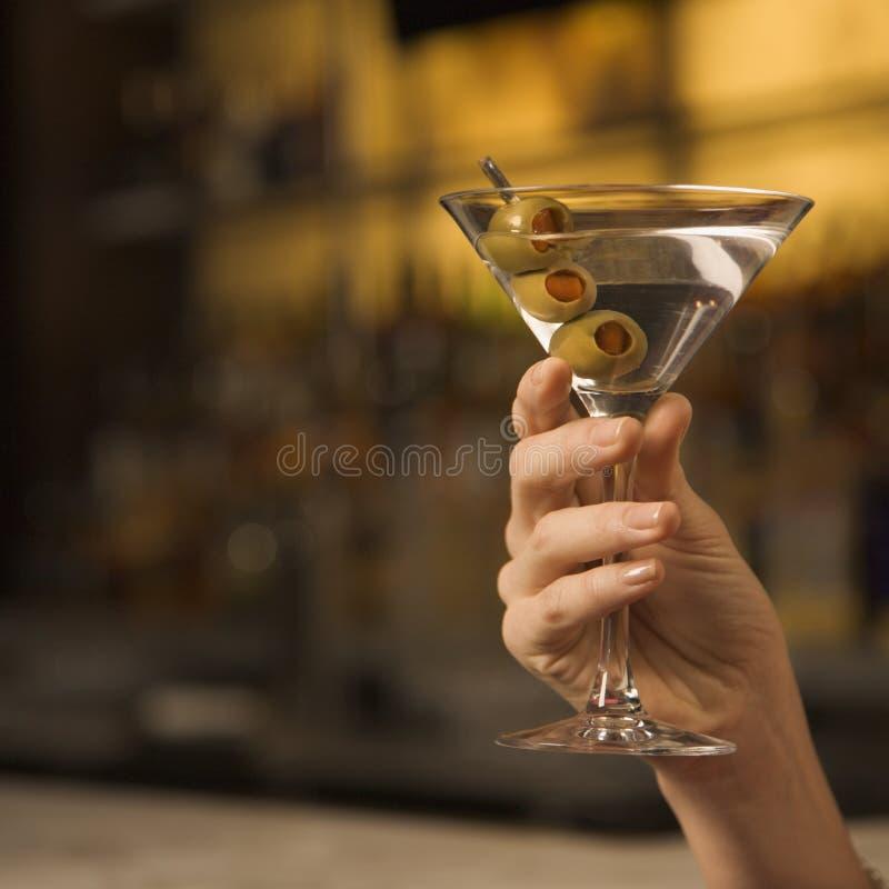 Terra arrendada fêmea martini da mão. imagem de stock royalty free