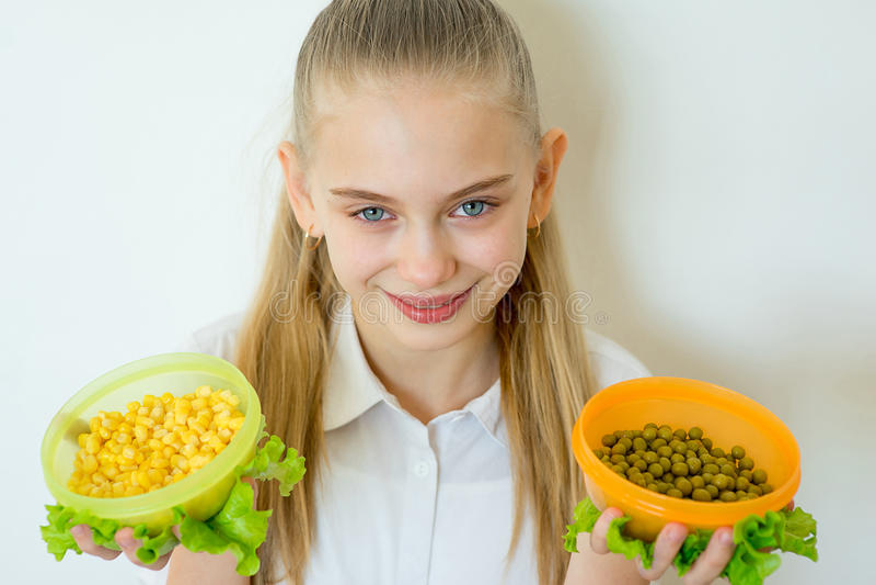 A terra arrendada feliz da menina da aptidão enlatou ervilhas e milho foto de stock