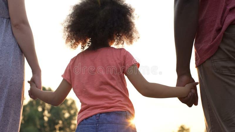 terra arrendada feminino Encaracolado-de cabelo suas mãos da mãe e do pai, felicidade na família fotografia de stock royalty free