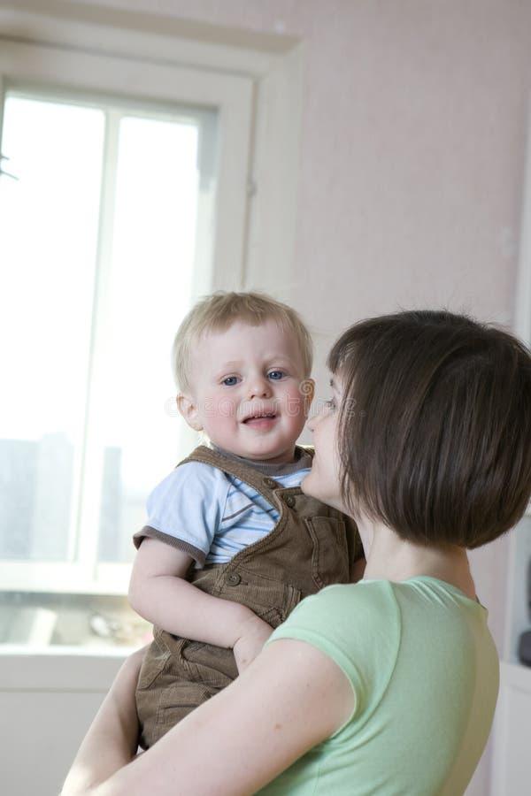 Terra arrendada loura feliz da matriz seu bebê de sorriso fotos de stock royalty free