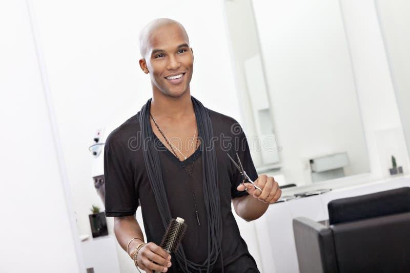 A terra arrendada masculina de sorriso do cabeleireiro scissor e escova de cabelo imagem de stock royalty free