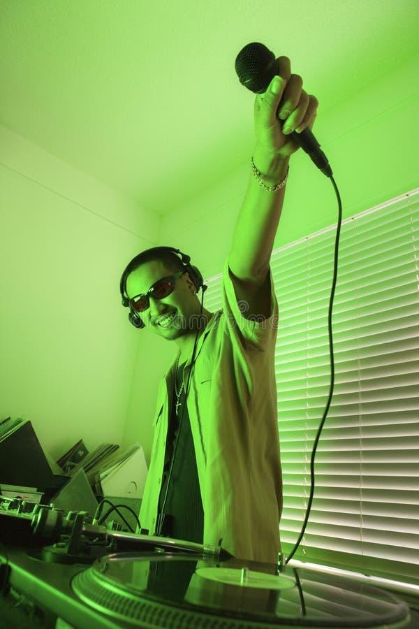 Terra arrendada masculina mic do DJ no ar. fotografia de stock royalty free