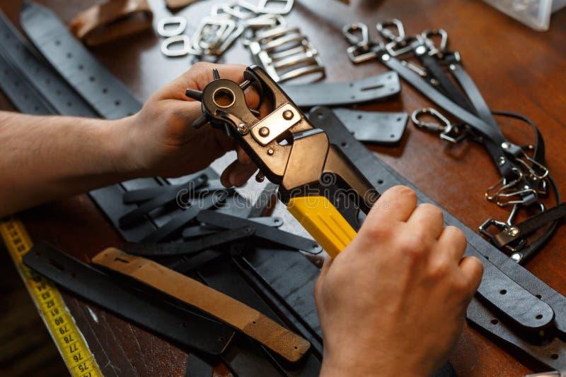 Terra arrendada mestra um perfurador de furo e uma parte de couro Na tabela de madeira marrom dispersou com ferramentas e acess?r fotos de stock royalty free