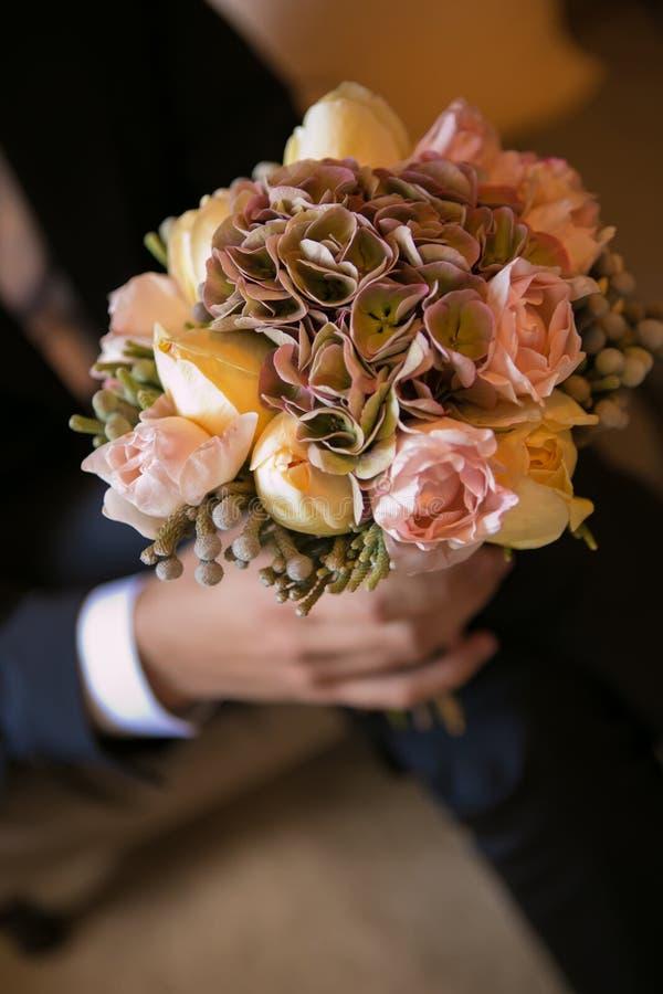 Terra arrendada nas mãos delicadas, ramalhete nupcial caro, na moda do noivo do casamento das flores imagem de stock