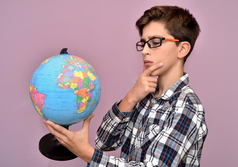 Terra arrendada nova do menino e exame do globo fotografia de stock royalty free