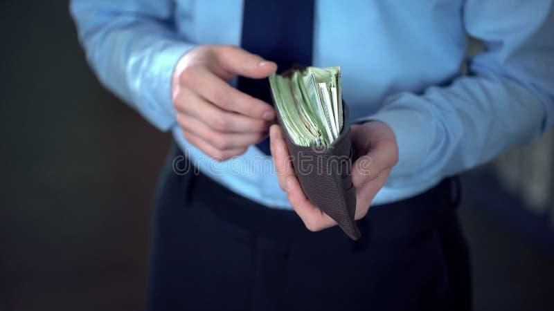 A terra arrendada rica do homem de negócios abriu a carteira de couro completamente de cédulas do dólar, finança fotos de stock