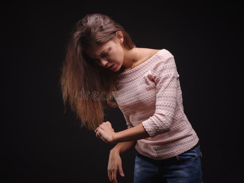 A terra arrendada triste da mulher tangled o cabelo no fundo preto Topete do cabelo em uma mão do ` s da menina Conceito da queda imagens de stock