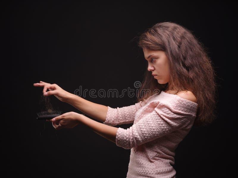 A terra arrendada triste da mulher tangled o cabelo no fundo preto Topete do cabelo em uma mão do ` s da menina Conceito da queda imagem de stock royalty free