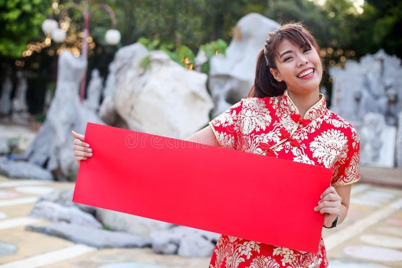 Terra arrendada vestindo da menina chinesa bonita e vermelho de papel vazio da mostra, ano novo chinês feliz festivo e conceito d imagens de stock royalty free