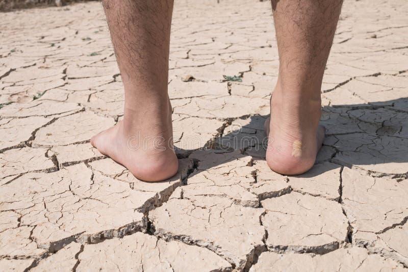Terra asciutta della crepa a piedi fotografia stock