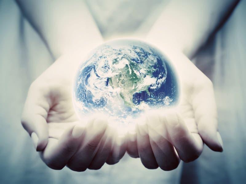 A terra brilha nas mãos da jovem mulher Salvar o mundo imagens de stock royalty free