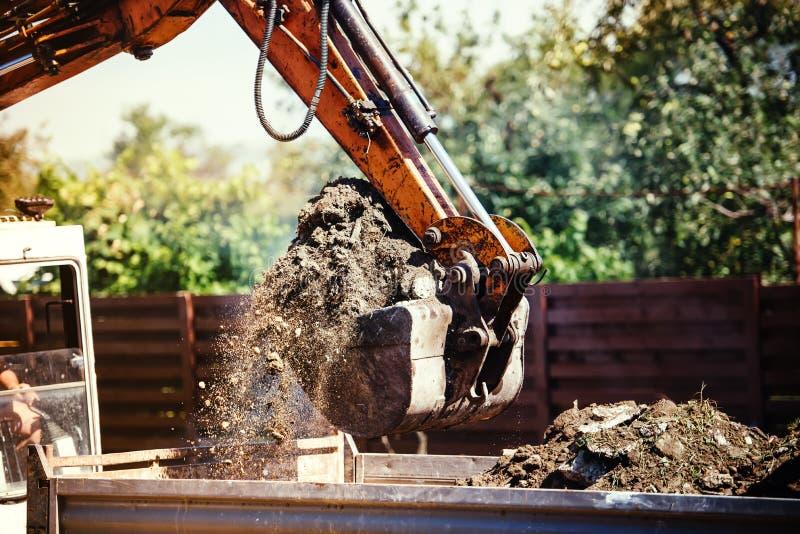 Terra commovente dell'escavatore dell'escavatore a cucchiaia rovescia sul cantiere fotografia stock