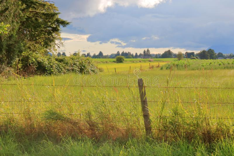 Terra de exploração agrícola e nuvens de chuva que varrem dentro imagens de stock royalty free