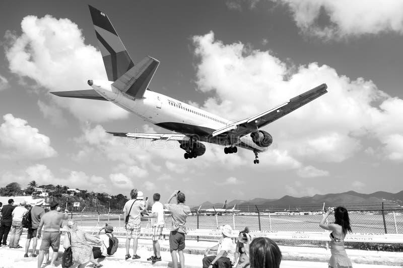 Terra dell'aereo dell'orologio della gente sull'aeroporto in Philipsburg, st Maarten fotografie stock libere da diritti