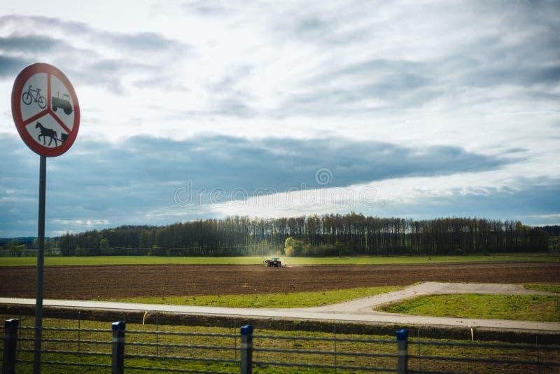 Terra di coltivazione del trattore in primavera, segno del trattore, cavallo e b immagini stock libere da diritti
