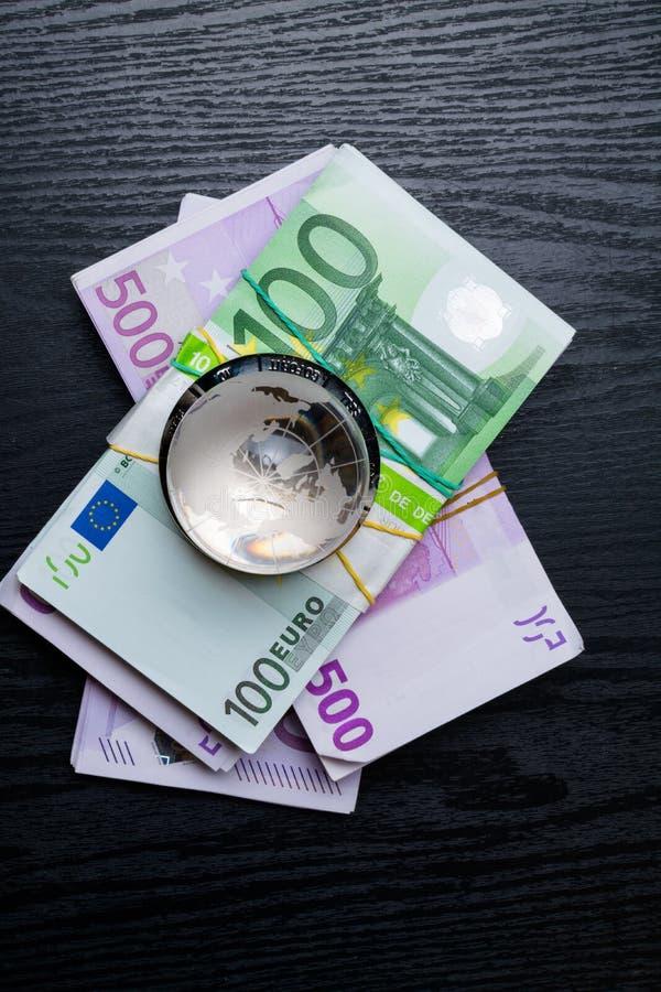 terra di vetro con gli euro contanti di quantità choice e grande sui precedenti di legno neri fotografia stock libera da diritti